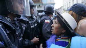 Indigenous protestor faces the riot police. She is much shorter and older than they are, and unarmed.