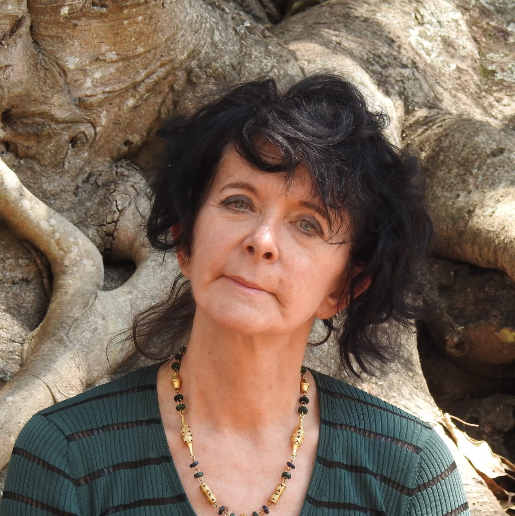 A portrait of the poet Ruth Padel in front of the roots of a tree.