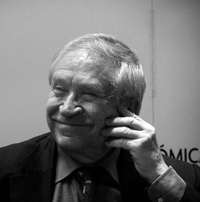 A black and white photograph of Mexican author Homero Aridjis, smiling.