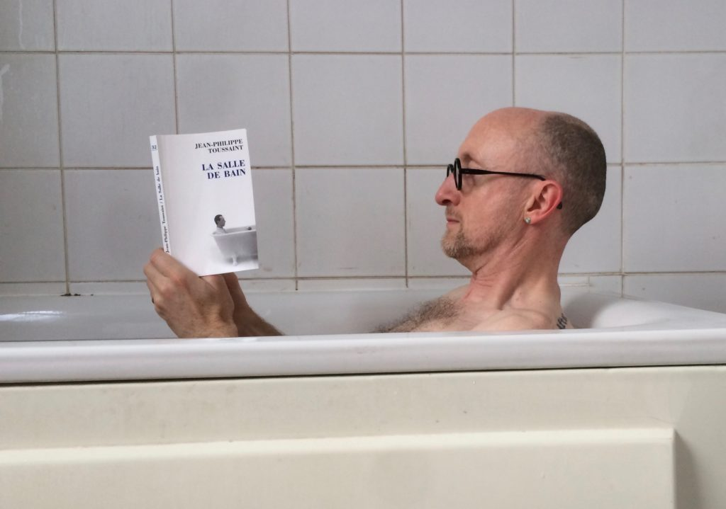 The author Nick Royle reading a book in the bath.