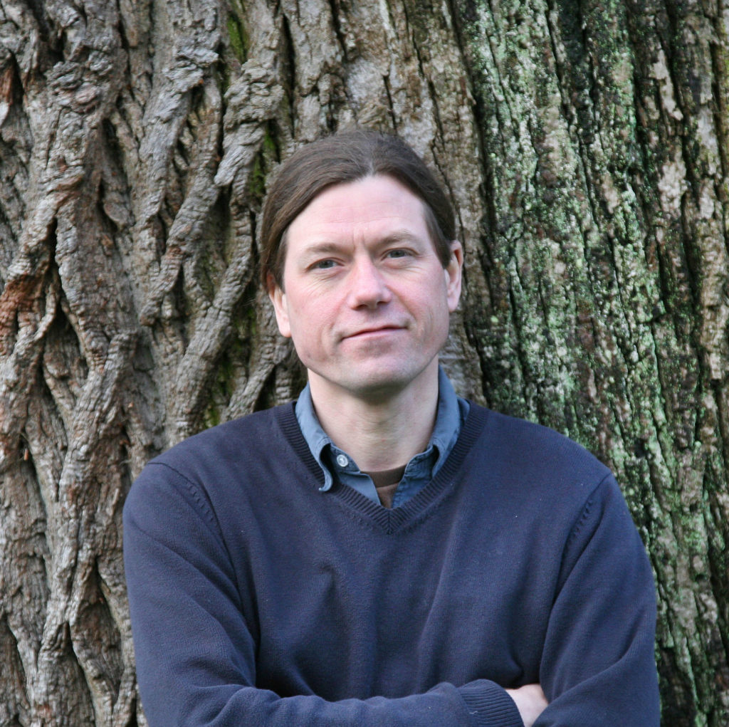 The author James Canton standing in front of the astonishing width of a large oak tree.
