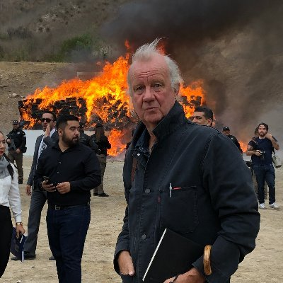 Ed Vuillamy in a leather jacket in front of a burning vehicle.