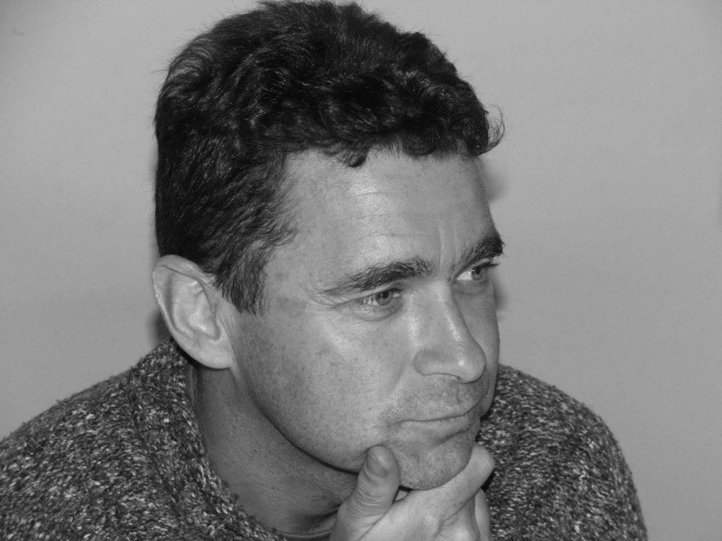 A black and white photograph of the poet David Butler looking thoughtful.