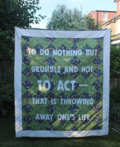 A quilt with the slogan 'To do nothing but grumble and not to act – that is throwing away one's life.'